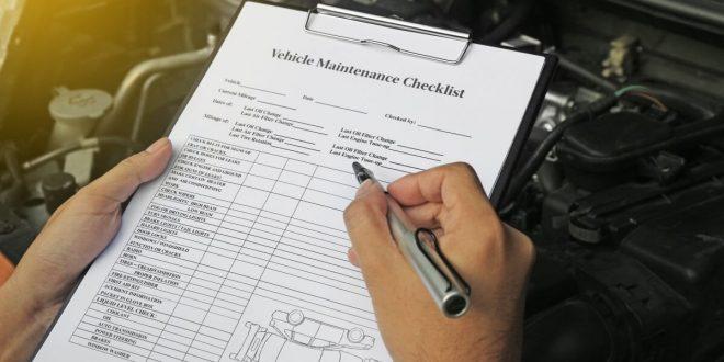 Auto mechanics using a vehicle maintenance checklist