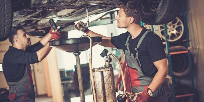 Two mechanics performing basic engine maintenance