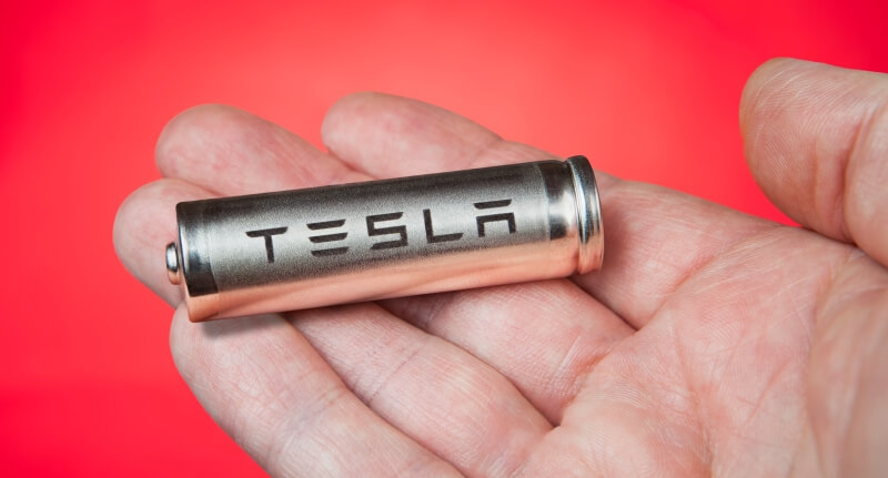 Hand holding a Tesla battery cell on red bacxkground