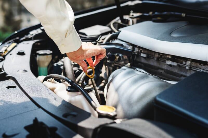 Man inspecting the engine oil level