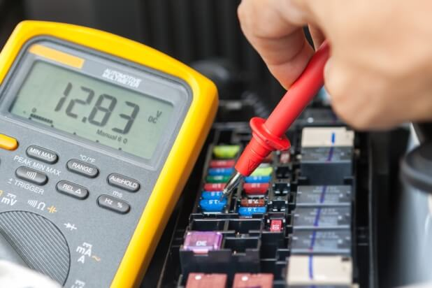 Auto mechanic testing an electrical circuit using a multimeter