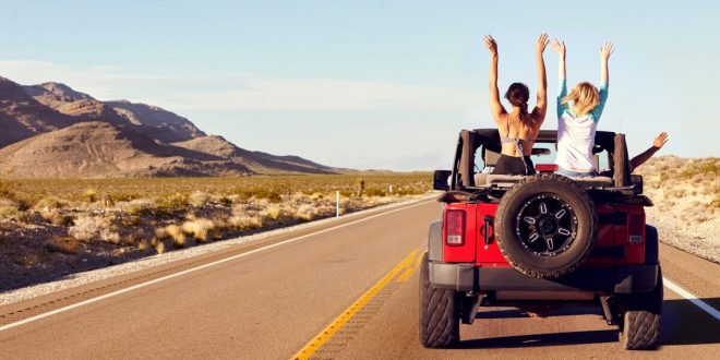 Group of friends on a road trip in a red Jeep Wrangler