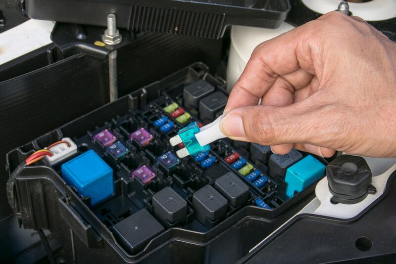 Auto mechanic removing a fuse