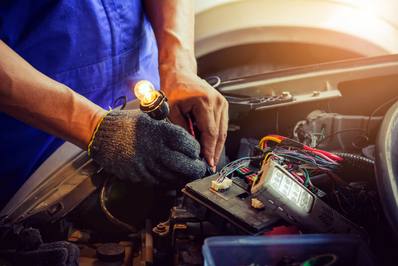 Auto mechanic testing an electrical circuit using a light bulb test light