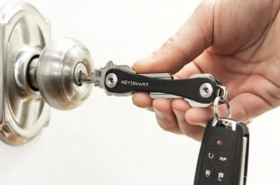 Person opening a door using a key on a key organizer
