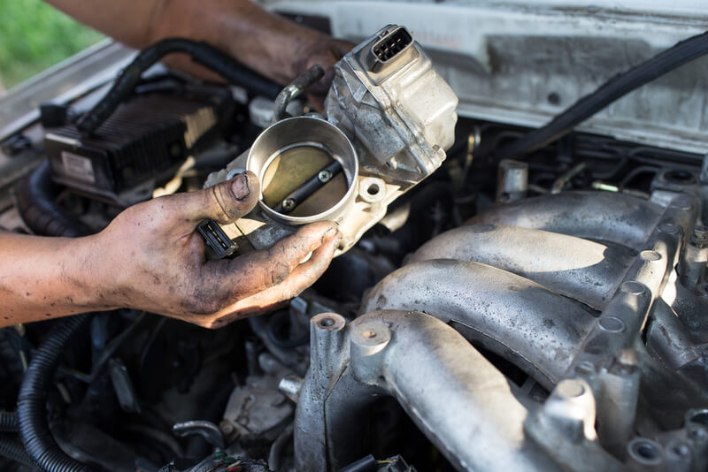 Auto mechanic doing a tune up on a throttle body