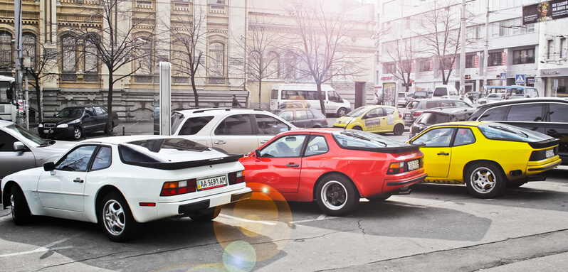 A white, a red and a yellow Pörsche 944 parked in a parking spot
