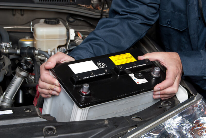 Mechanic removiong a car battery