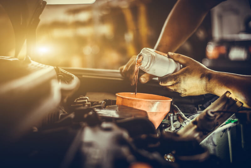 Mechanic adding engine oil