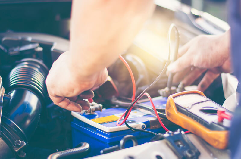 Auto mechanic testing a car battery using a multimeter