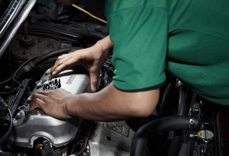 Auto mechanic reinstalling a valve cover