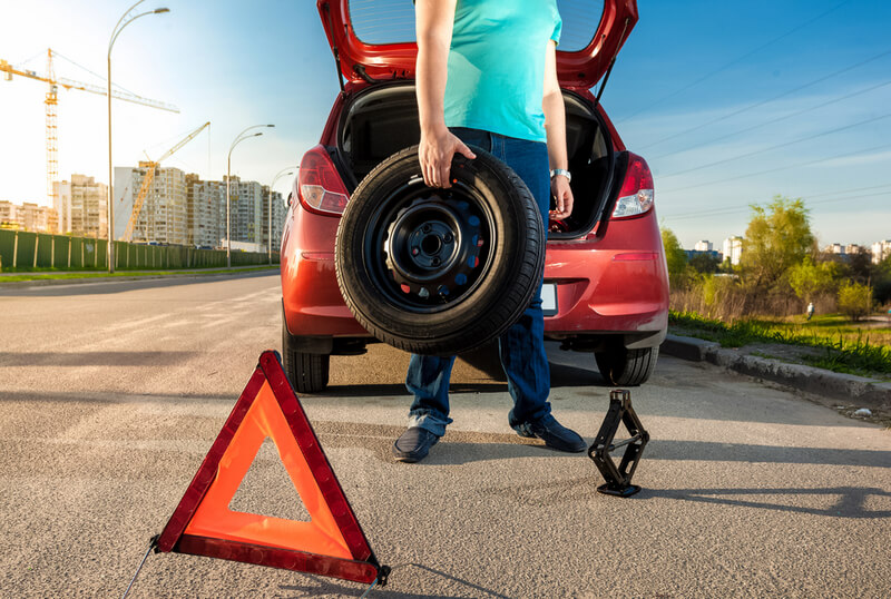 Man using reflective triangle to safely change a car tire