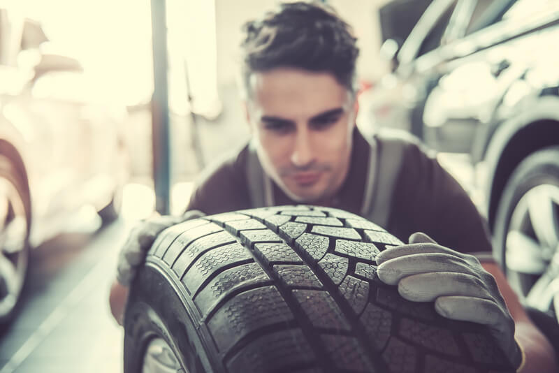 Auto mechanic inspecting a tire for flat