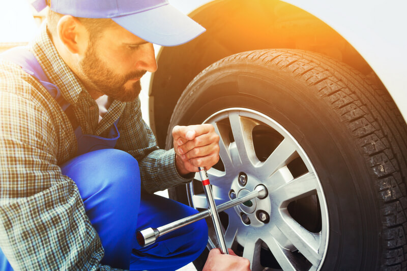Man tightening a wheel after changing a car tire