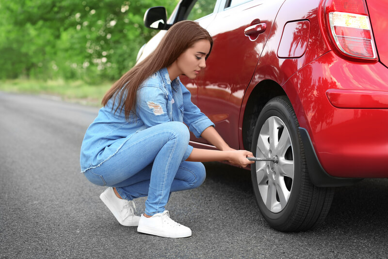 Woman uses a wrench to remove a car tire