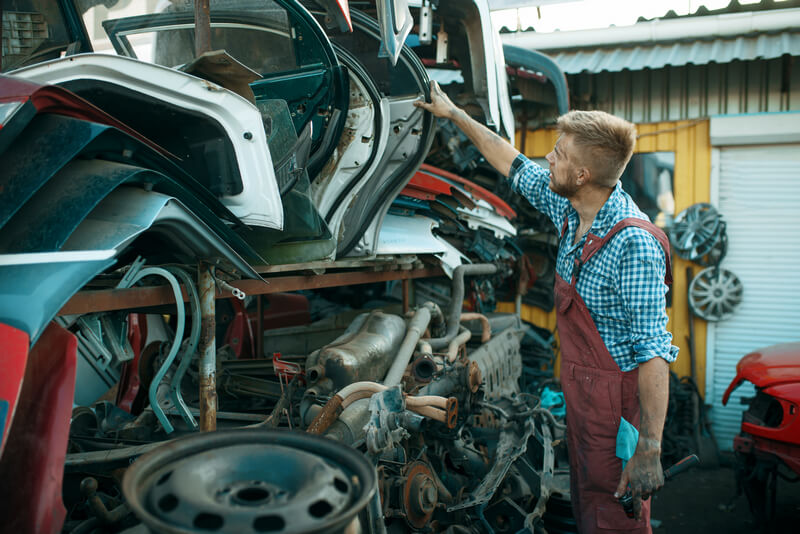 Mechanic looking at junked automotive parts