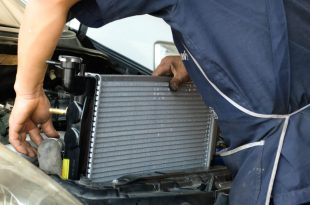 Auto mechanic replacing a car radiator