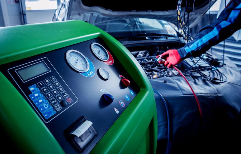 Auto mechanic servicing AC system