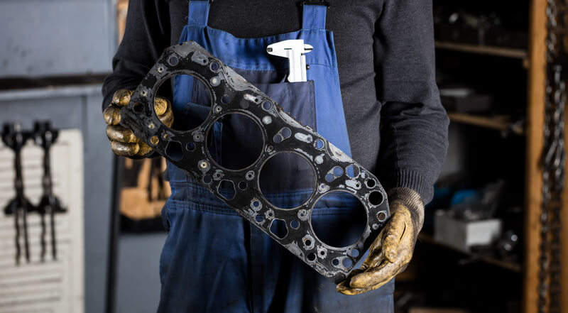Mechanic holding a leaking head gasket