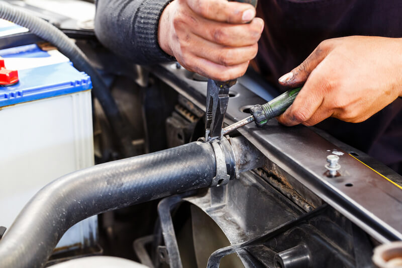Auto mechanic repairing a radiator