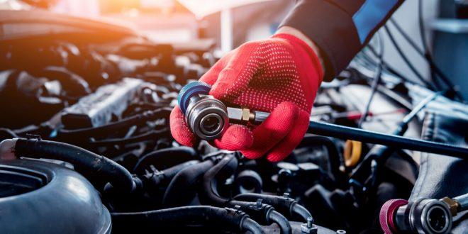 Auto mechanic repairing a car AC system