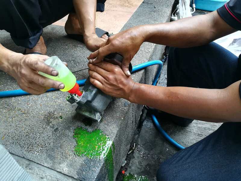 Mechanics replacing an AC compressor