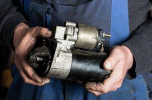 Auto mechanic replacing a starter