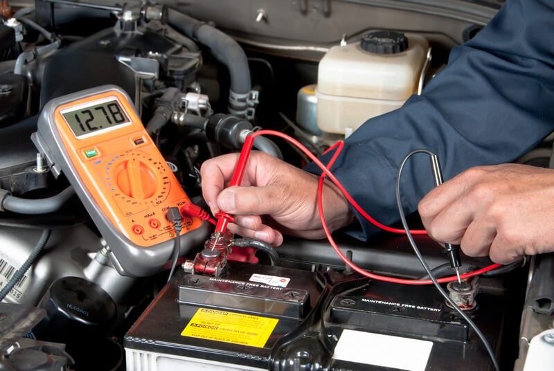 Auto mechanic testing a car battery