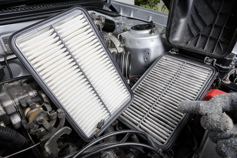 Auto mechanic replacing an air filter